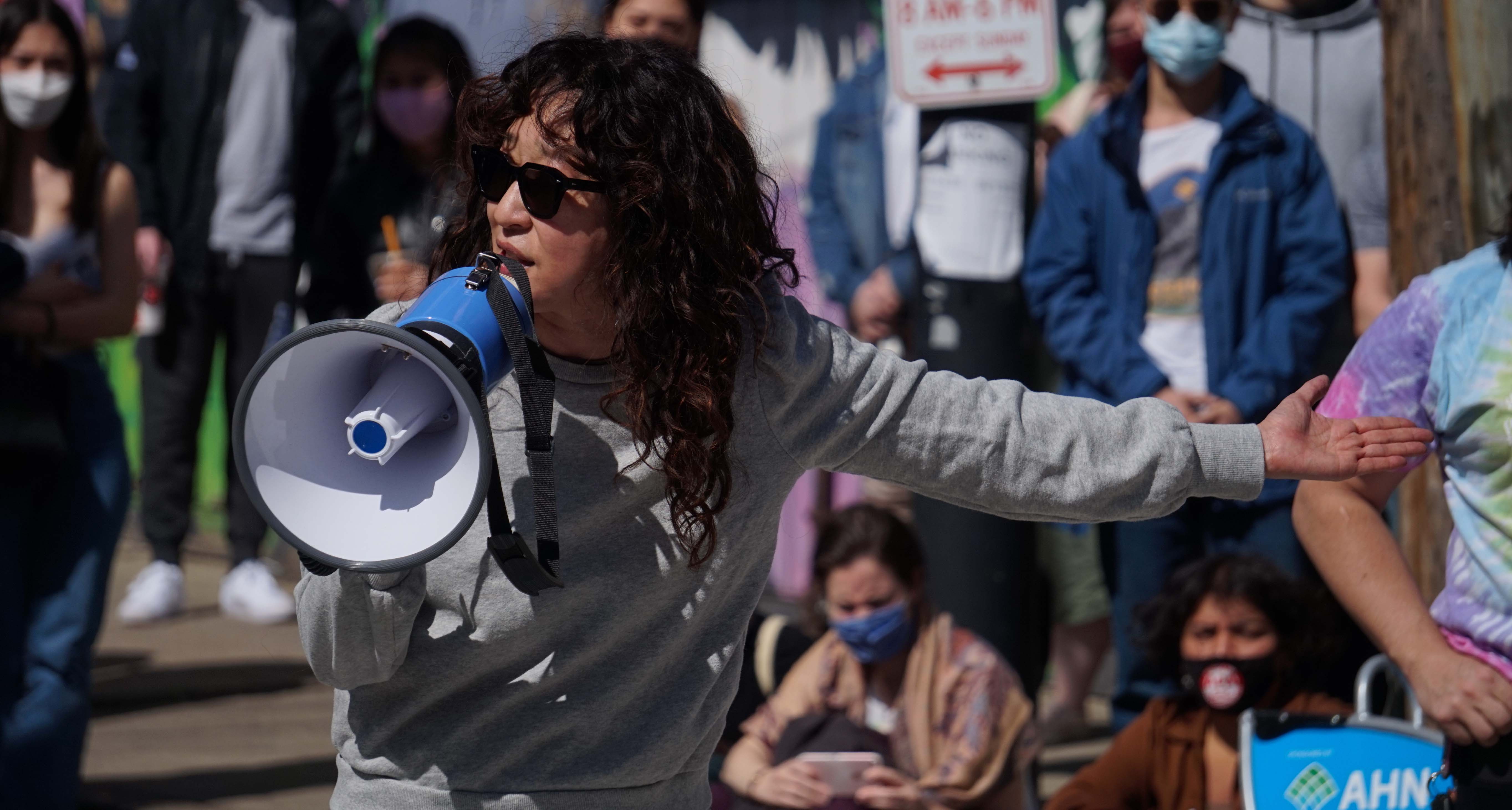 Woman addressing crowd with bullhorn