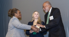 Kathy Humphrey handing award to Malik G. Bankston, executive director, Kingsley Association;