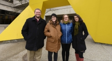 4 people near large yellow metal sculpture
