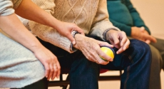 Person holding arm of elderly person