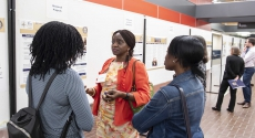 Abimbola Fapohunda Part-Time Faculty, Department of Africana Studies, in front of poster presentationis