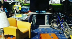 Parking space filled with carpet, chairs, bike, TV