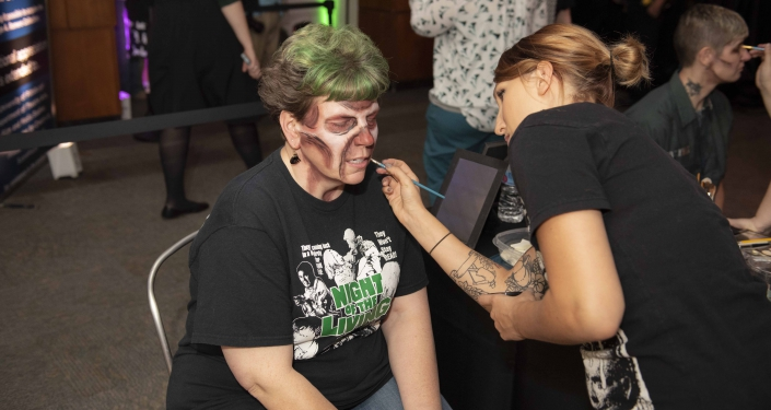 Woman being made up to look like a zombie