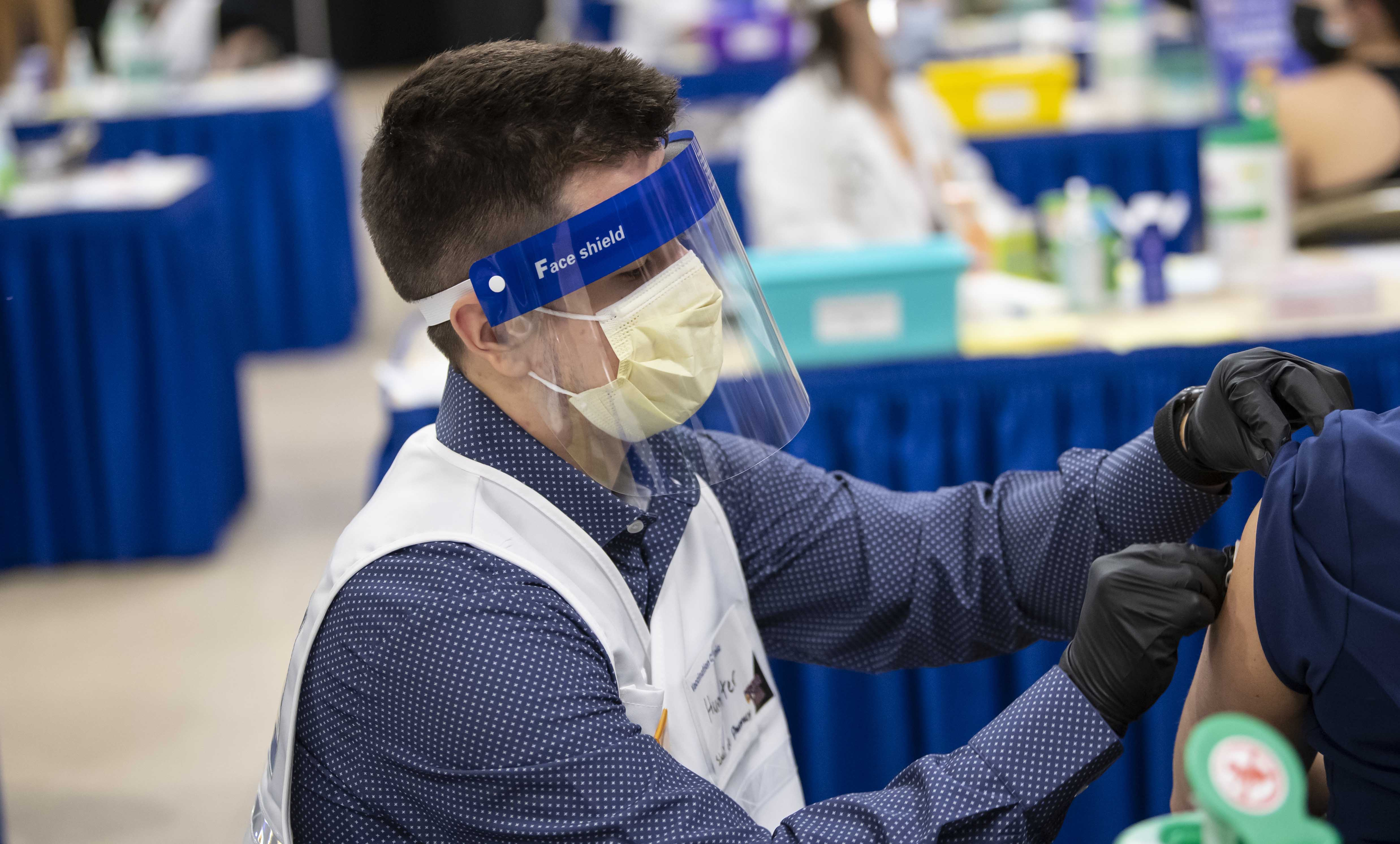 Man in face shield giving vaccine