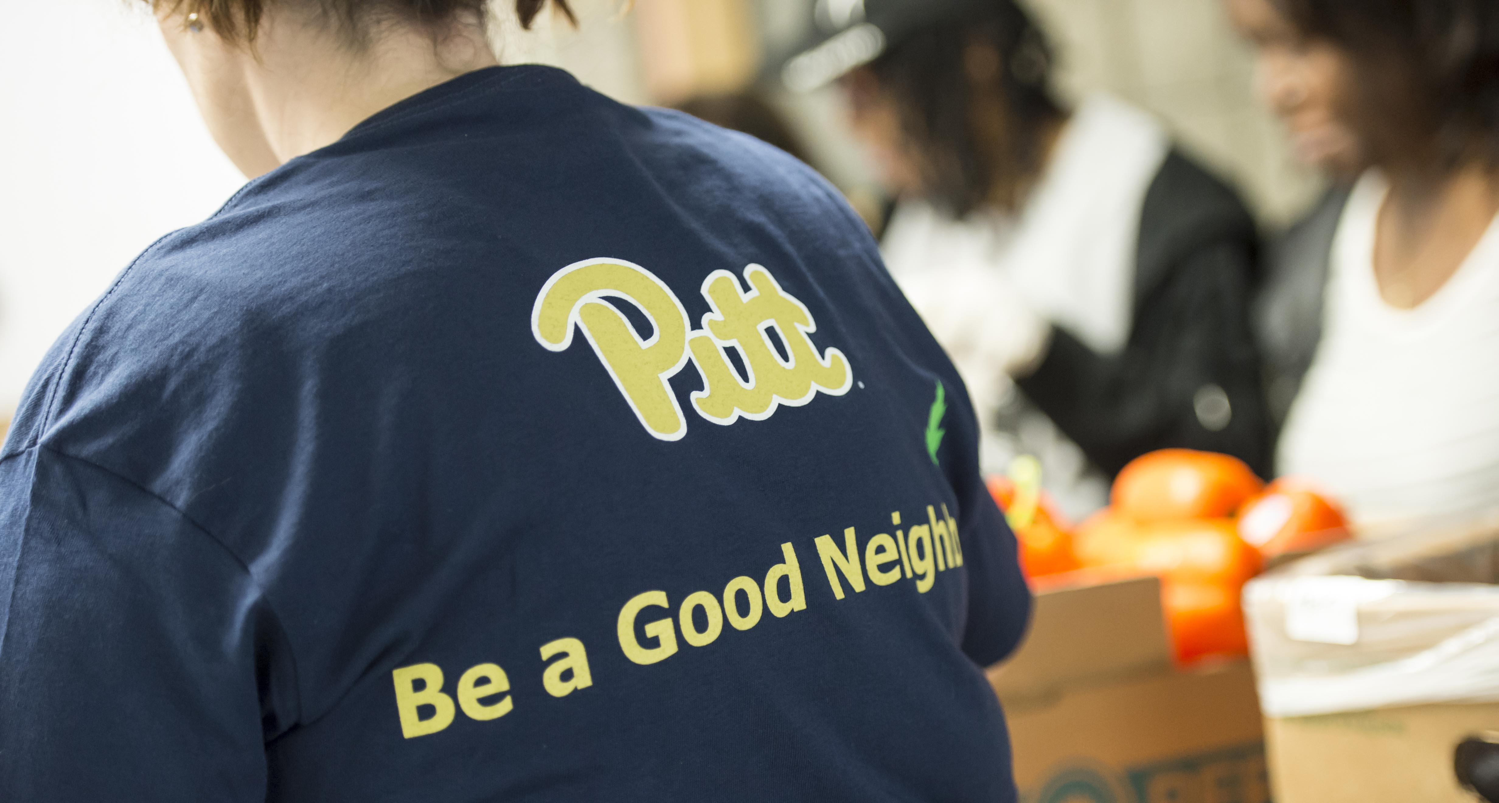Pitt volunteer with Be a Good Neighbor t-shirt