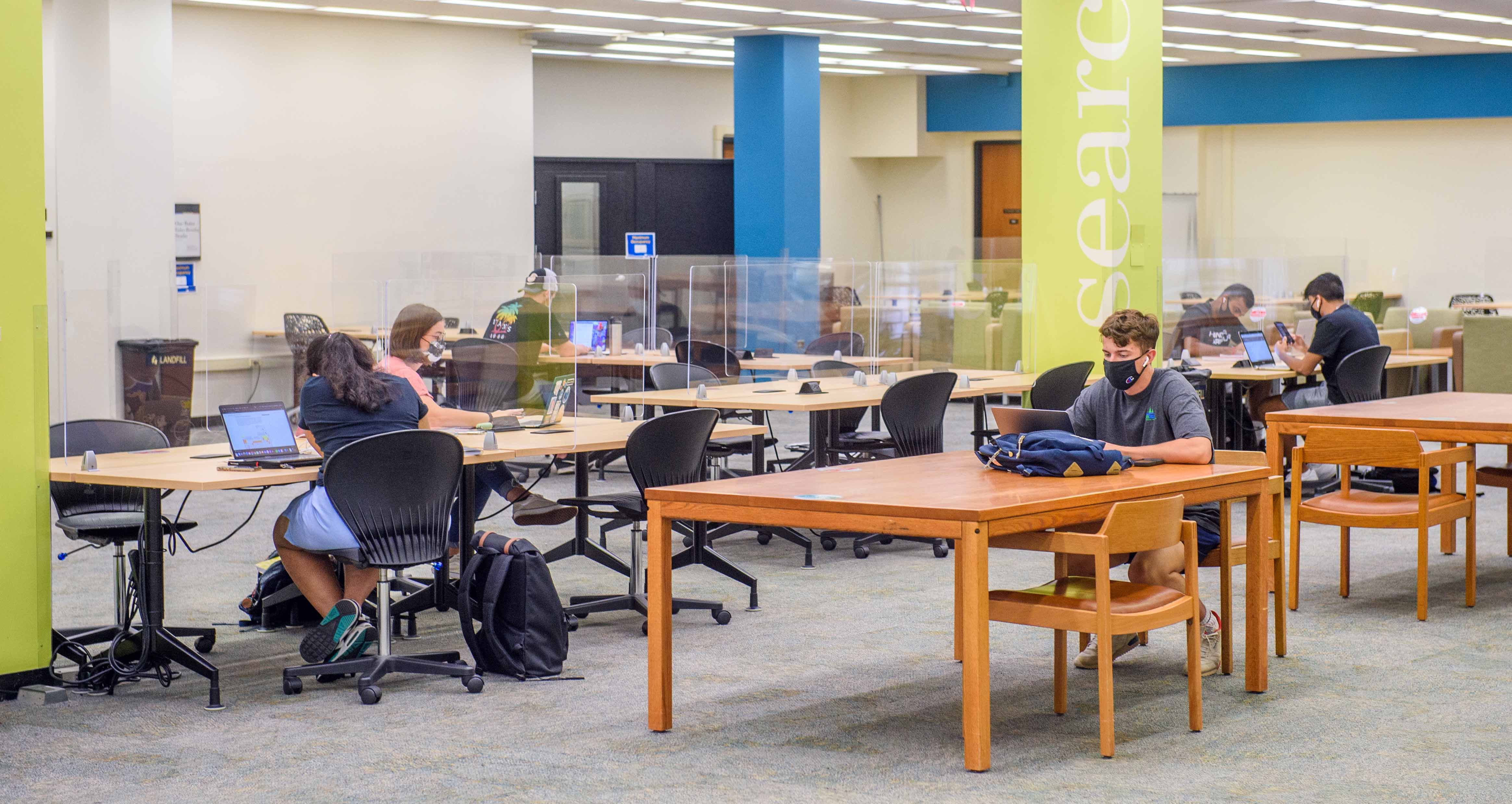 tables and students on ground floor of Hillman Library