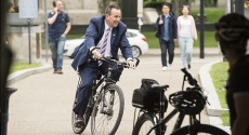 Kevin Sheehy riding bike in suit