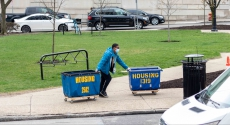 Student in mask moving out with housing bins