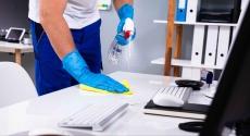 Hands cleaning a desktop