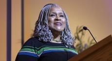 Kathy Humphrey in striped dress at podium