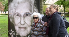 Holocaust survivor in front of her portrait