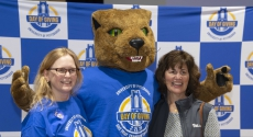 Panther mascot Roc standing between two women