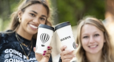 Two students holding Saxbys cups