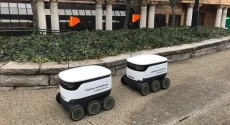 Two rolling robots wait outside William Pitt Union