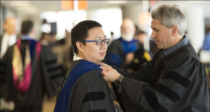 Pu Song gets his gown hood adjusted by Ivan Yotov