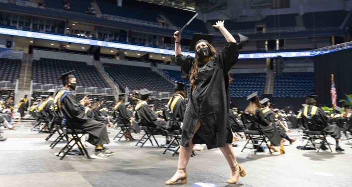 Student celebrating in graduation gown