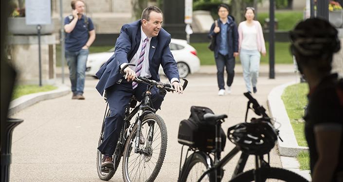 Kevin Sheehy riding bike on Schenley Plaza