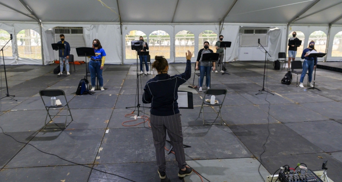 Woman directing Heinz Chapel Choir members in tent